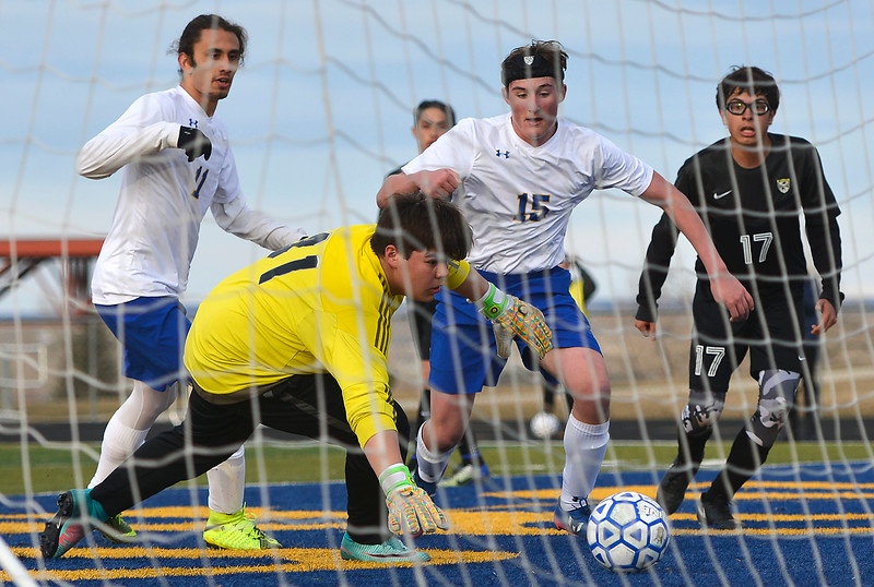 Justin Sheely   The Sheridan Press<br /> Sheridan's Bryce Taylor, left, passes to Sam Smart (15) for a goal against Cheyenne South's keeper Isaiah Reynolds, center, and Rodrigo Velazquez (17) at Homer Scott Field Friday, March 23, 2018. The Broncs fell 3-1.