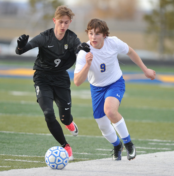 Tibby McDowell | The Sheridan Press<br /> Sheridan's Quinn Heyneman, right, battles for the ball against Cheyenne South's Tyler Flynn at Homer Scott Field Friday, March 23, 2018.