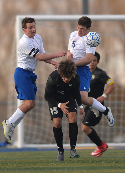 Justin Sheely   The Sheridan Press<br /> Sheridan's Kyle Custis, left, and Garrett Coon, right, go for a header against Cheyenne South's Joel Young at Homer Scott Field Friday, March 23, 2018. The Broncs fell 3-1.
