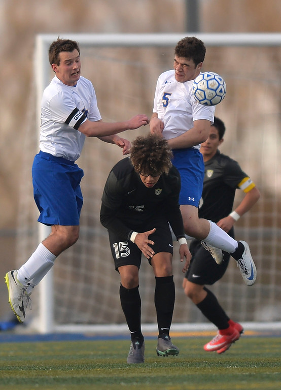 Justin Sheely | The Sheridan Press<br /> Sheridan's Kyle Custis, left, and Garrett Coon, right, go for a header against Cheyenne South's Joel Young at Homer Scott Field Friday, March 23, 2018. The Broncs fell 3-1.