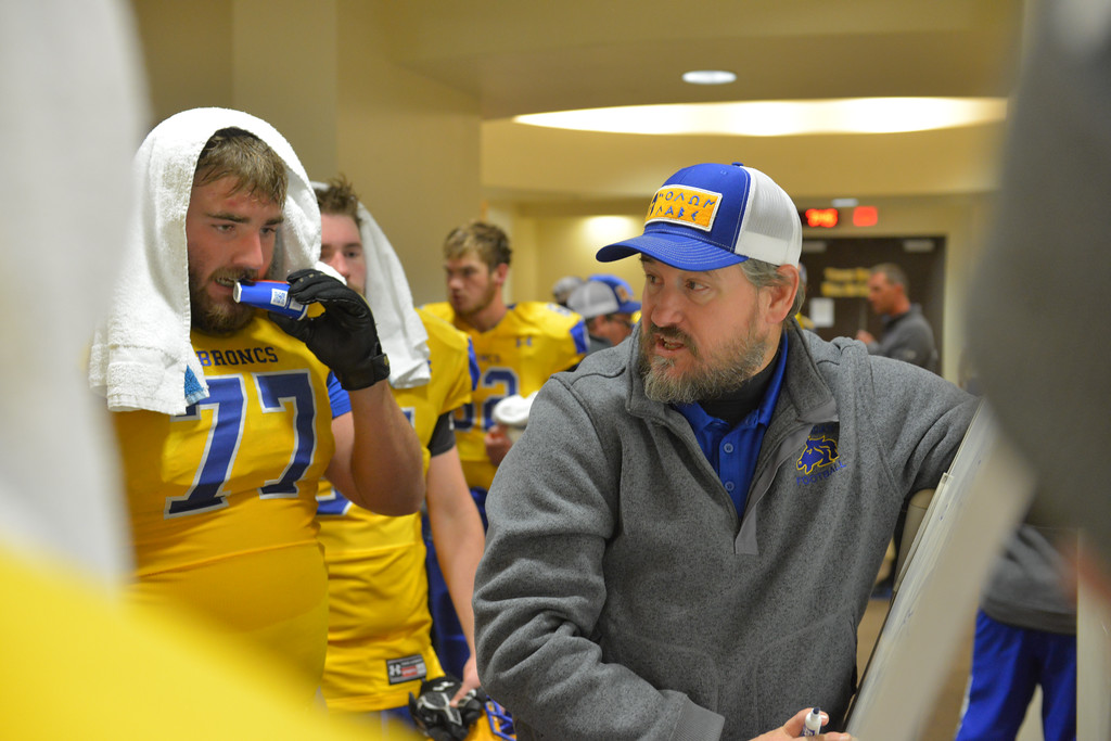 Justin Sheely | The Sheridan Press<br /> Coach Kevin Rizer runs over some strategies with Blayne Baker and linemen in the locker room at halftime during the class 4A state championship match against Natrona County High School Saturday, November 11, 2017, at War Memorial Stadium in Laramie. The Broncs claimed their third-straight state title after beating the Mustangs 28-14. The Sheridan Broncs were undefeated for their season.