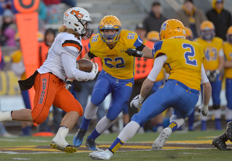 Justin Sheely | The Sheridan Press<br /> Sheridan's Quinton Brooks (62) and Aaron Sessions (2) close in on Mustangs' Brett Brenton during the class 4A state championship match against Natrona County High School Saturday, November 11, 2017, at War Memorial Stadium in Laramie. The Broncs claimed their third-straight state title after beating the Mustangs 28-14. The Sheridan Broncs were undefeated for their season.