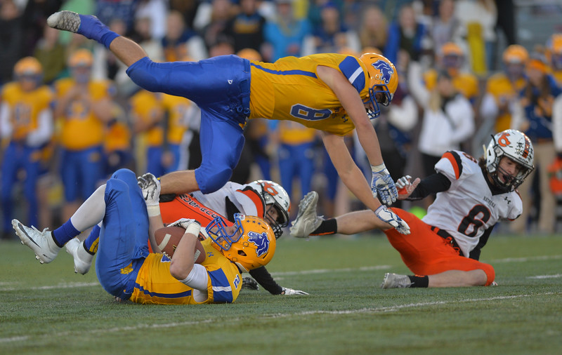 Justin Sheely | The Sheridan Press<br /> Sheridan's Samuel Boyles tumbles over Aaron Session and Mustangs' Cooper Quig during the class 4A state championship match against Natrona County High School Saturday, November 11, 2017, at War Memorial Stadium in Laramie. The Broncs claimed their third-straight state title after beating the Mustangs 28-14. The Sheridan Broncs were undefeated for their season.
