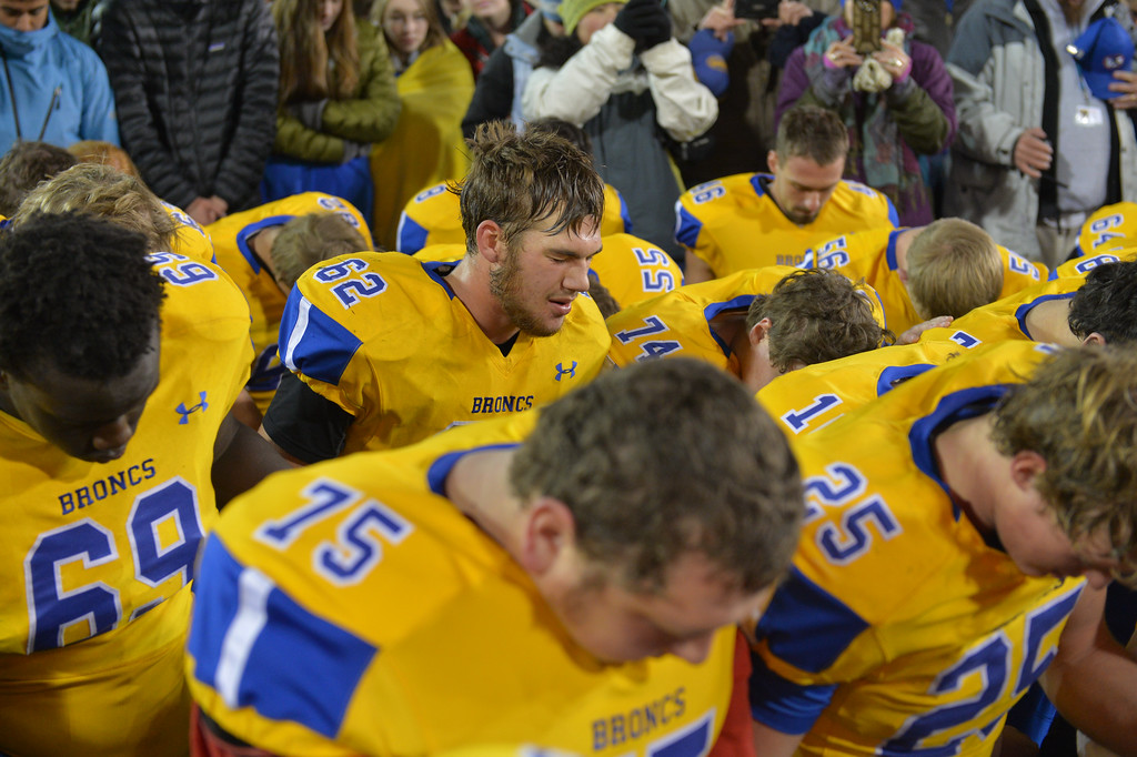Justin Sheely | The Sheridan Press<br /> Quinton Brooks leads the group in a thankful prayer in the class 4A state championship match against Natrona County High School Saturday, November 11, 2017, at War Memorial Stadium in Laramie. The Broncs claimed their third-straight state title after beating the Mustangs 28-14. The Sheridan Broncs were undefeated for their season.
