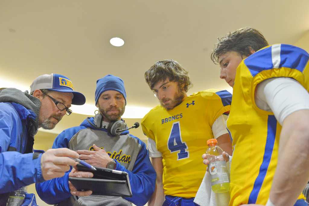Justin Sheely | The Sheridan Press<br /> Broncs head coach Don Julian, left, coach Jeff Mowry and quarterback Aaron Woodward and wide receiver Aaron Sessions look at video during the class 4A state championship match against Natrona County High School Saturday, November 11, 2017, at War Memorial Stadium in Laramie. The Broncs claimed their third-straight state title after beating the Mustangs 28-14. The Sheridan Broncs were undefeated for their season.