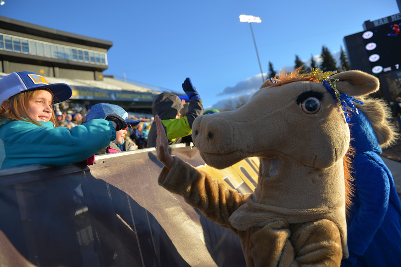 Justin Sheely | The Sheridan Press<br /> Seven-year-old Lydia Dearcorn high-fives a Lady Bronc mascott during the class 4A state championship match against Natrona County High School Saturday, November 11, 2017, at War Memorial Stadium in Laramie. The Broncs claimed their third-straight state title after beating the Mustangs 28-14. The Sheridan Broncs were undefeated for their season.