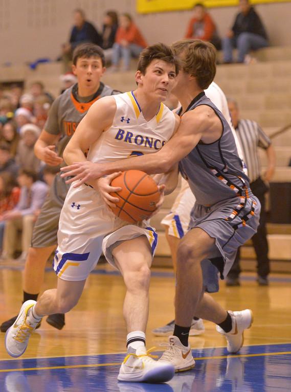 Justin Sheely | The Sheridan Press<br /> Sheridan's Aaron Sessions draws a foul from Mustang's Brennan Hagar at Sheridan High School Friday, Dec. 22, 2017. Broncs won 64-50.