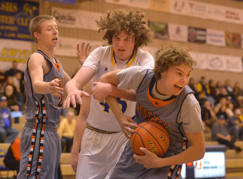 Justin Sheely | The Sheridan Press<br /> Sheridan's Samuel Lecholat, center, tries to rebound against Natrona High School's Brett Norvelle, left, and Ben Acres at Sheridan High School Friday, Dec. 22, 2017. Broncs won 64-50.