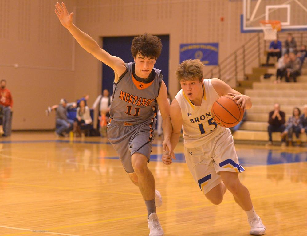 Justin Sheely | The Sheridan Press<br /> Sheridan's Tristan Bower, right, drives the ball against Natrona High School's Jhett George at Sheridan High School Friday, Dec. 22, 2017. Broncs won 64-50.