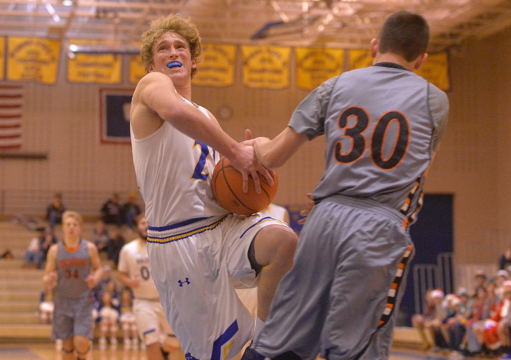 Justin Sheely | The Sheridan Press<br /> Sheridan's Parker Christensen is fouled by Natrona High School's Brennan Hagar at Sheridan High School Friday, Dec. 22, 2017. Broncs won 64-50.