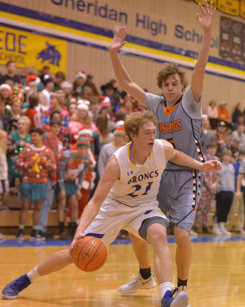 Justin Sheely | The Sheridan Press<br /> Sheridan's Parker Christensen drives the ball against Natrona High School's Ben Acres at Sheridan High School Friday, Dec. 22, 2017. Broncs won 64-50.