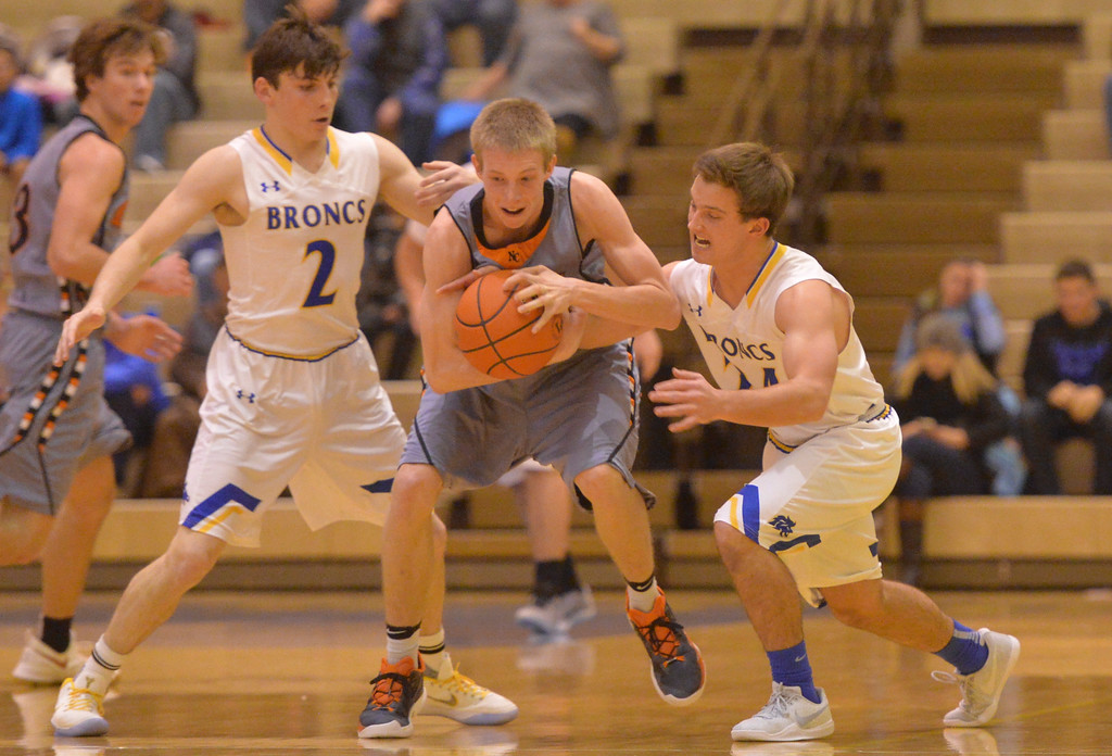 Justin Sheely | The Sheridan Press<br /> Sheridan's Aaron Sessions, left, and Kyle Custis try to strip the ball from Mustang's Brett Norvelle Sheridan High School Friday, Dec. 22, 2017. Broncs won 64-50.