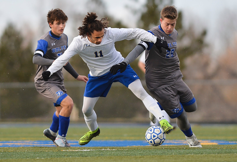 Justin Sheely | The Sheridan Press<br /> Sheridan's Bryce Taylor, center, battles Thunder Basin's Isaac Howell, left, and Logan MacKearney at Homer Scott Field Friday, April 13, 2018. The Broncs lost 2-1.