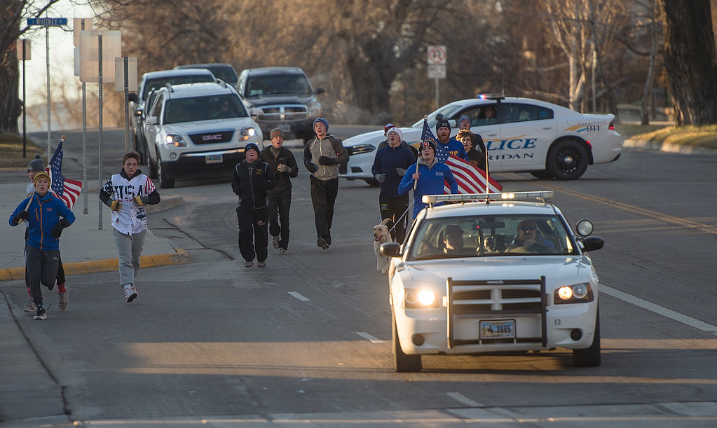Justin Sheely | The Sheridan Press	<br /> The Broncs wrestling team chase the Sheridan Police Department car as it rolls downhill Saturday morning on Main Street. The Sheridan High School wrestling team begin their season with the tradition of pushing a police car from the station to the Sheridan County Courthouse and back.