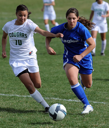 Katy Hedlund, left, of Niwot, and Kayla baker of Broomfield, chase down the ball.<br /> <br /> Cliff Grassmick / April 15, 2010