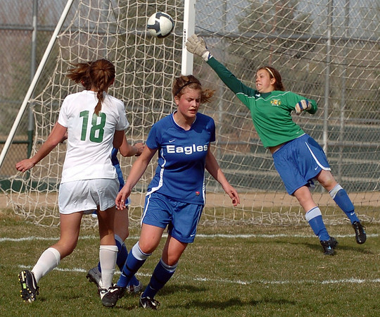 Broomfield keeper, Caitlin Updyke, goes up to block a shot by Kelsey Blessing of Niwot.<br /> <br /> Cliff Grassmick / April 15, 2010