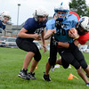 """Connor Leyet is tackled by David Mueller while practicing a drill during the Broomfield Youth Football Association combine on Thursday, Aug. 2, at the Broomfield Commons Park red field in Broomfield. For more photos of the football camp go to  <a href=""""http://www.dailycamera.com"""">http://www.dailycamera.com</a><br /> Jeremy Papasso/ Camera"""