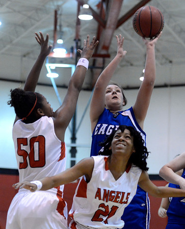 "Broomfield High School's Stacie Hull takes a shot over Khadijah Vigil, left, and Jau'Nae Peevy during a game against Denver East on Saturday, Dec. 15, at Fairview High School in Boulder. For more photos of the game go to  <a href=""http://www.dailycamera.com"">http://www.dailycamera.com</a><br /> Jeremy Papasso/ Camera"