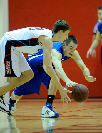 Broomfield's Dakota Smith (right) and Heritage's Trevor Adamson (left)race for a loose ball during their basketball game in the Fairview Festival at Fairview High School in Boulder, Colorado December 11, 2009.  CAMERA/Mark Leffingwell