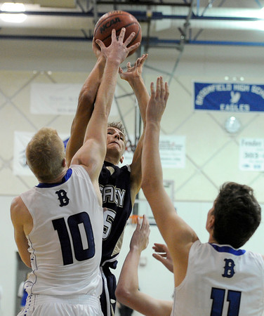 Legacy High School's Mitchell McCall takes a shot over Dan Perse, left, and Spenser Reeb on Tuesday, Nov. 4, during a game against Broomfield High School at Broomfield. Broomfield won the game.<br /> Jeremy Papasso/ Camera