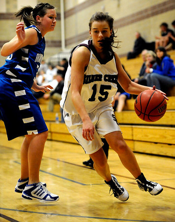 Silver Creek's Jacy Drobney (right) takes the ball around Broomfield's Millie Reeves (left) during their basketball game Silver Creek High School in Longmont, Colorado December 15, 2009.  CAMERA/Mark Leffingwell