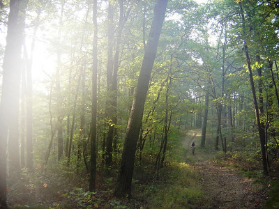 The sunrise effuses this photo of a mountain biker riding a trail in Brown County, Indiana.