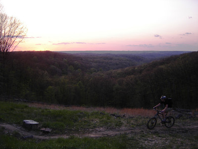 This rider finishes the 2.5 mile long Hesitation Point climb in Brown County State Park as the sun sets in the distance.