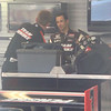 Hélio Castroneves talks to a crew member in the garage.