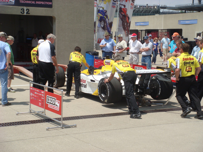 Car being rolled into technical inspection in the garage area.