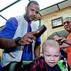 CC Sabathia shears the golden locks of little Adonis Colon of the South Bronx as Jordan Sports Barbershop barber, Guillermo Leon in uniform orange, looks on.