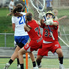 "Centaurus High School's Emma Lazaroff (20) scores against Regis Jesuit High School's goalie Emily Smith (33) as Erin Schilmoeller (7) defends during their game in Lafayette Thursday. <br /> For more photos from the game go to  <a href=""http://www.bocopreps.com"">http://www.bocopreps.com</a><br /> Photo by Paul Aiken / The Camera / April 12, 2011"