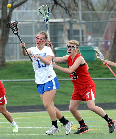 """Centaurus High School's Carley Dvorak (13) passes against Regis Jesuit High School's Rachel Deits (13) during their game in Lafayette Thursday. <br /> For more photos from the game go to  <a href=""""http://www.bocopreps.com"""">http://www.bocopreps.com</a><br /> Photo by Paul Aiken / The Camera / April 12, 2011"""