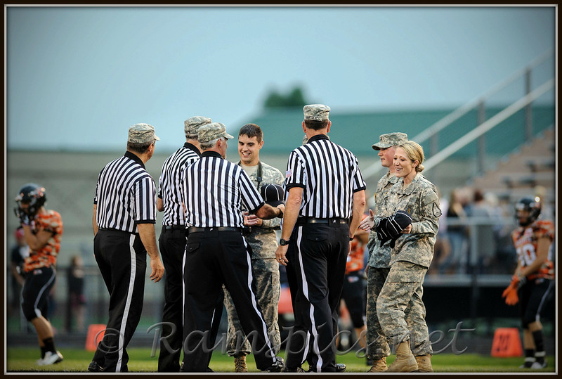 Members of the Army National Guard exchange caps with the officiating crew, prior to the start of the Charlotte (MI) vs Eaton Rapids varsity football game.<br /> Officials wore the caps (each bearing the name of a veteran) for the entire game... in the back ground, home team CHS Orioles warm up in commemorative uniforms, Friday September 7, 2012.