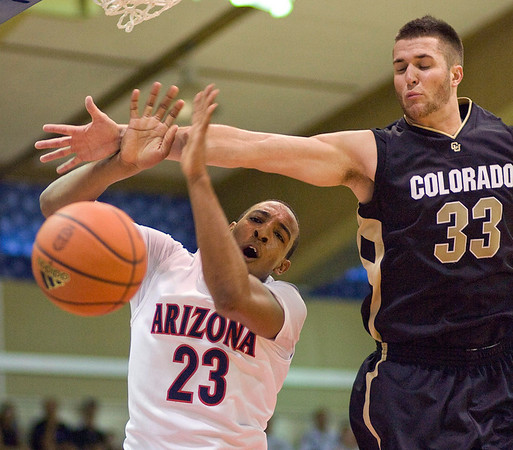 Arizona forward Derrick Williams (23) is fouled from behind by Colorado forward Austin Dufault (33) in the first half of an NCAA college basketball game Tuesday, Nov. 24, 2009, at the Maui Invitational in Lahaina, Hawaii. (AP Photo/Eugene Tanner)