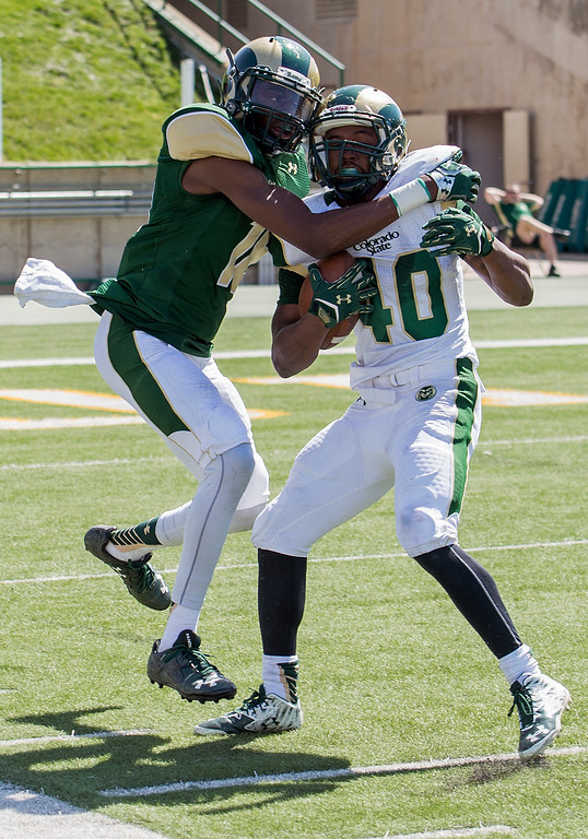 . Rams defensive back Braylin Scott (18) catches running back Johnathan Lewis (40) along the sideline for a tackle Saturday afternoon April 23, 2016 during the 2016 Green and Gold Spring Game at Hughes Stadium in Fort Collins. (Photo by Michael Brian/Loveland Reporter-Herald)