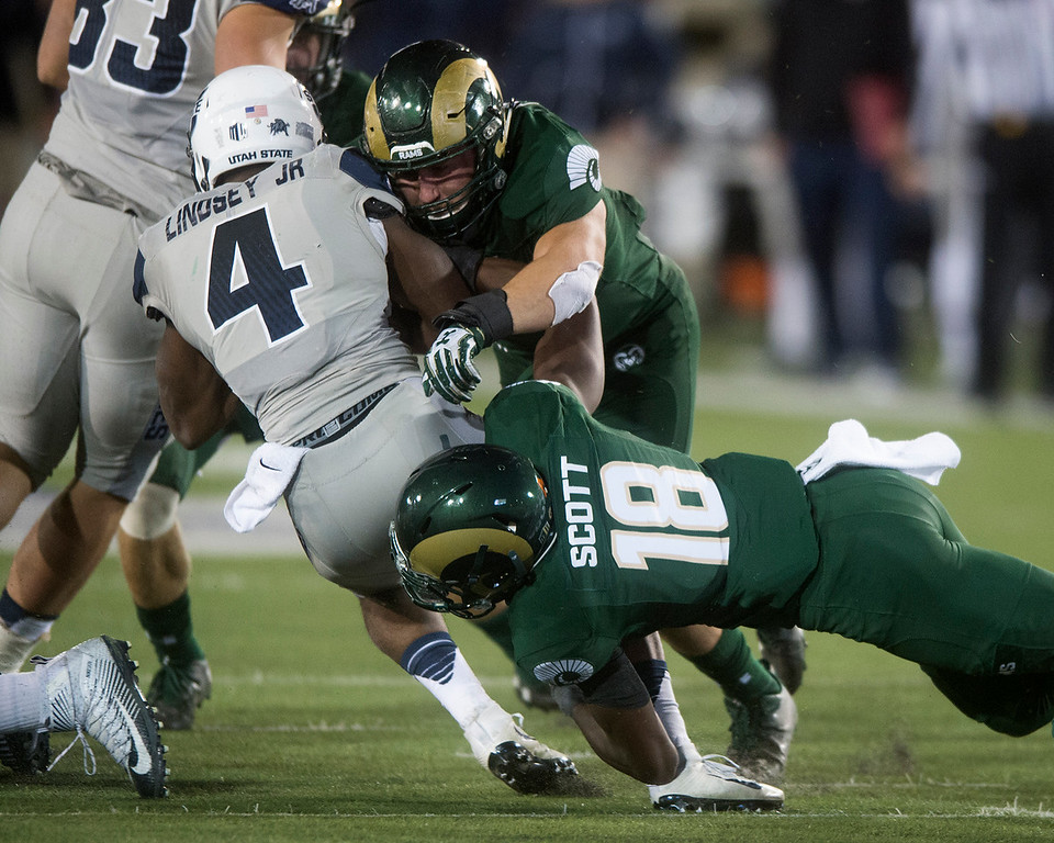 . Colorado State linebacker Evan Colorito (43) and defensive back Braylin Scott (18) tackle Utah State Tonny Lindsey, Jr., Saturday evening Oct. 8, 2016 at Hughes Stadium in Fort Collins. (Photo by Michael Brian/Loveland Reporter-Herald)