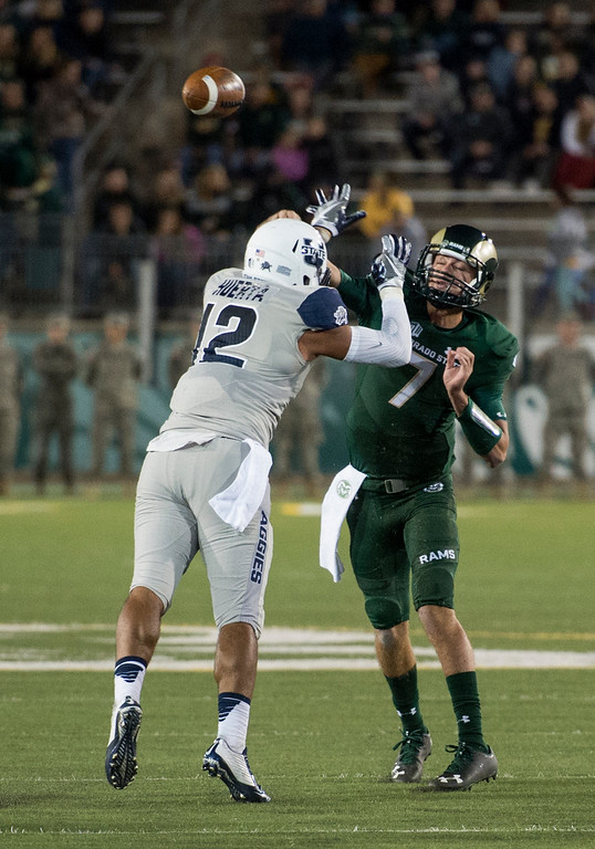 . Colorado State quarterback Nick Stevens (7) throws with Utah State linebacker Alex Huerta (12) in his face Saturday evening Oct. 8, 2016 at Hughes Stadium in Fort Collins. (Photo by Michael Brian/Loveland Reporter-Herald)
