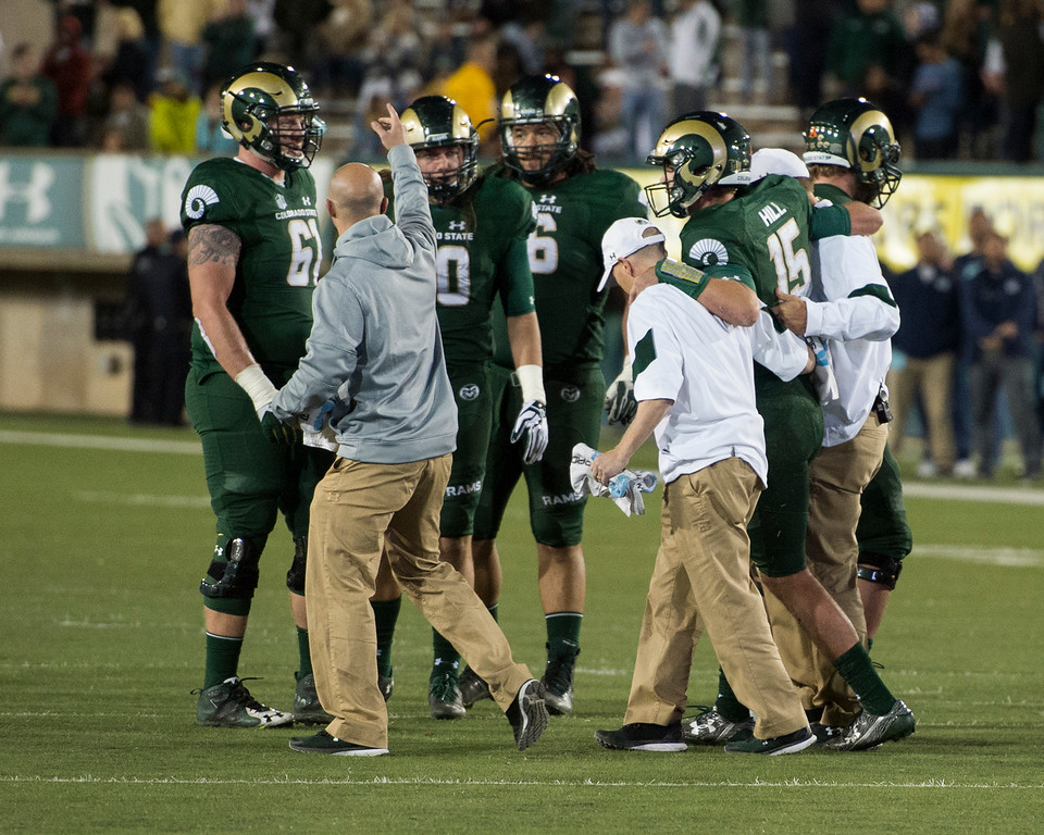 . Colorado State starting quarterback Collin Hill (15) gets helped off the field after sustaining an injury scrambling from the pocket against Utah State Saturday evening Oct. 8, 2016 at Hughes Stadium in Fort Collins. (Photo by Michael Brian/Loveland Reporter-Herald)