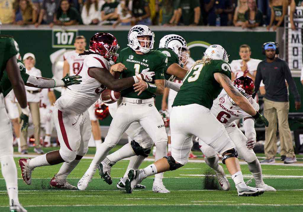 . Colorado State quarterback K.J. Carta-Samuels (1) has the ball stripped from his grip by an Arkansas defender Saturday evening Sept., 8, 2018 at Canvas Stadium in Fort Collins. The Rams came from behind to win, 34-27. (Michael Brian/For the Reporter-Herald)