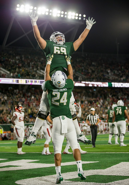 . Colorado State running back Izzy Matthews (24) and offensive lineman Barry Wesley (69) celebrate the winning touchdown over Arkansas Saturday evening Sept., 8, 2018 at Canvas Stadium in Fort Collins. The Rams came form behind to win 34-27. (Michael Brian/For the Reporter-Herald)