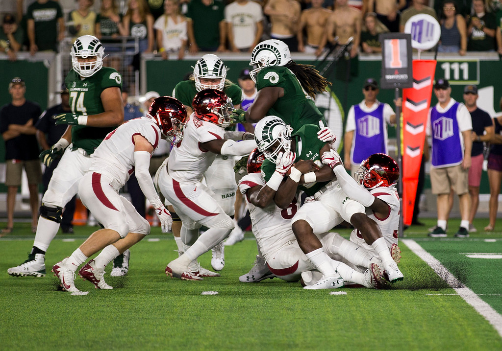 . Colorado State running back Rashaad Boddie (28) gets drug down by two Arkansas defenders during the second half Saturday evening Sept., 8, 2018 at Canvas Stadium in Fort Collins. The Rams beat the Razorbacks, 34-27. (Michael Brian/For the Reporter-Herald)