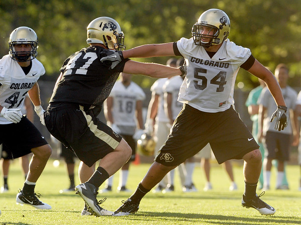 "University of Colorado's Brady Daigh, right, shakes off an offensive lineman on Friday, Aug. 5, during the Buff's second football practice on the University of Colorado practice field in Boulder. For more photos and interviews from the practice go to  <a href=""http://www.dailycamera.com"">http://www.dailycamera.com</a><br /> Jeremy Papasso/ Camera"