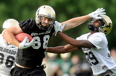 University of Colorado tight end Kyle Slavin gives a nasty stiff arm to cornerback Josh Moten  on Thursday, Aug. 4, during the Buff's first football practice on the University of Colorado practice field in Boulder. For more photos and interviews from the practice go to www.dailycamera.com Jeremy Papasso/ Camera