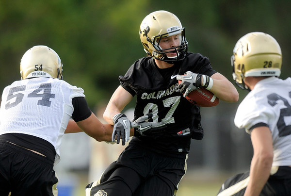 "University of Colorado wide receiver Tyler McCulloch shakes a tackle from Kaiwi Crabb, No. 54, on Thursday, Aug. 4, during the Buff's first football practice on the University of Colorado practice field in Boulder. For more photos and interviews from the practice go to  <a href=""http://www.dailycamera.com"">http://www.dailycamera.com</a><br /> Jeremy Papasso/ Camera"