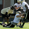 University of Colorado defensive line coach Kanavis McGhee watches Nick Kasa, middle, as he tries to hit Stephane Nembot from his knees on Saturday, Aug. 6, at the CU Buff's third practice of the season.<br /> Jeremy Papasso/ Camera