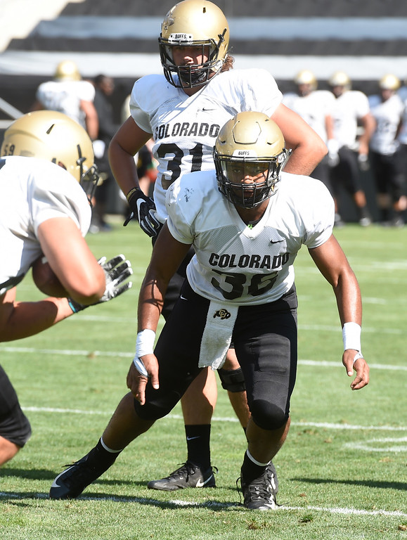 . Boulder, CO - AUGUST 11:   Jonathan Van Diest, top, and Akil Jones, during the University of Colorado football scrimmage on August 11, 2018.(Photo by Cliff Grassmick/Staff Photographer)