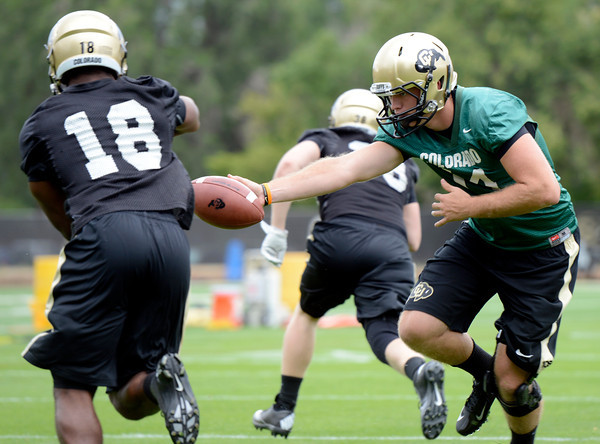 """University of Colorado quarterback John Schrock hands the ball off to Donta Abron during football practice on Monday, Aug. 6, at the CU practice field in Boulder. For more photos of the practice go to  <a href=""""http://www.dailycamera.com"""">http://www.dailycamera.com</a><br /> Jeremy Papasso/ Camera"""