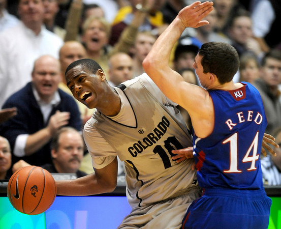 Colorado's Alec Burks (left) gets fouled by Kansas' Tyrel Reed (right)during their game at the University of Colorado in Boulder, Colorado January 24, 2011.  CAMERA/Mark Leffingwell