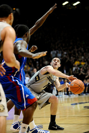 Colorado's Nate Tomlinson (right) passes the ball around Kansas' Elijah Johnson (left) during their game at the University of Colorado in Boulder, Colorado January 24, 2011.  CAMERA/Mark Leffingwell