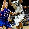 Colorado's Alec Burks (right) jumps past Kansas' Brady Morningstar (left) during their game at the University of Colorado in Boulder, Colorado January 24, 2011.  CAMERA/Mark Leffingwell
